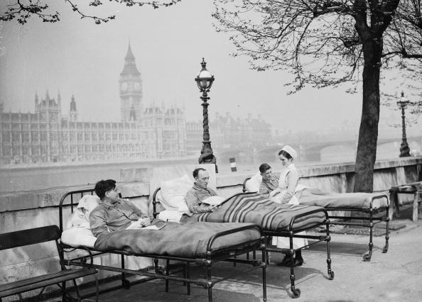 May 1936:  Tuberculosis patients from St. Thomas' Hospital rest in their beds in the open air by the River Thames, opposite the Houses of Parliament.  (Photo by Fox Photos/Getty Images)