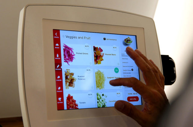 "SAN FRANCISCO, CA - AUGUST 31: A customer uses an interactive kiosk to place orders at eatsa, a fully automated fast food restaurant on August 31, 2015 in San Francisco, California. eatsa, an automated fast food restaurant that has no servers, wait staff and a virtual cashier that offers fresh quinoa bowls opened in San Francisco's Financial District. Customers place their orders at an interactive kiosk and then pick their orders at a first of its kind automated food pick-up system that features a collection of glass door ""cubbies"" with a door that displays personalized graphics and presents the food at the touch of a button. (Photo by Justin Sullivan/Getty Images)"