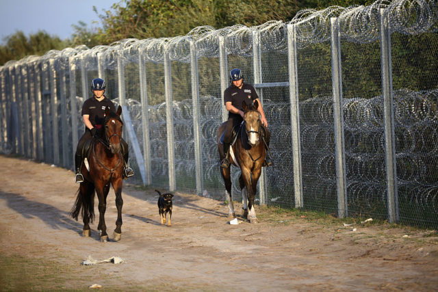 ROSZKE, HUNGARY - SEPTEMBER 14:  Hungarian police on horses patrol the Hungarian-Serbian border fence after the open rail track crossing was closed on September 14, 2015 in Roszke, Hungary. Hungary implements new laws to administer the influx of migrants and become enforceable tonight. Since the beginning of 2015 the number of migrants using the so-called 'Balkans route' has exploded with migrants arriving in Greece from Turkey and then travelling on through Macedonia and Serbia before entering the EU via Hungary. The number of people leaving their homes in war torn countries such as Syria, marks the largest migration of people since World War II.  (Photo by Christopher Furlong/Getty Images)