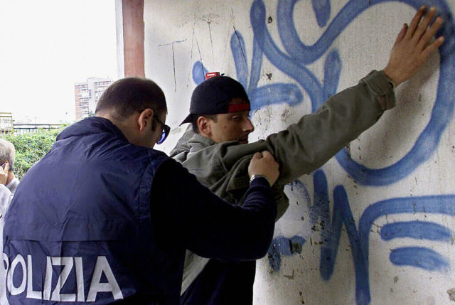 NAPLES, ITALY:  A policeman searches a man suspected of being in the mafia during a huge ongoing operation involving hundreds of police officers, early 07 December 2004 in Naples. Ciro Di Lauro, son of a Camorra (local mafia) godfather Paolo Di Lauro, is one of 53 Mafia suspects who were taken into police custody Tuesday as part of a massive police swoop to staunch the bloodletting in a turf war which has killed more than 120 people.   AFP PHOTO/CARLO HERMANN  (Photo credit should read CARLO HERMANN/AFP/Getty Images)