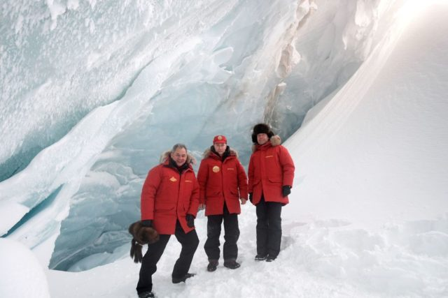 Russian President Vladimir Putin (C), Defense Minister Sergei Shoigu (R) and Prime Minister Dmitry Medvedev pose for a picture as they visit an ice cavern on Alexandra Land Island in the remote Arctic islands of Franz Josef Land on March 29, 2017. / AFP PHOTO / POOL / Alexei Druzhinin (Photo credit should read ALEXEI DRUZHININ/AFP/Getty Images)