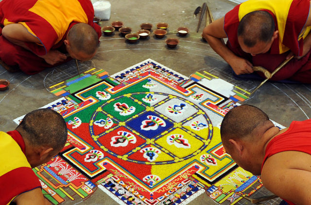 Tibetan Buddhist monks prepare a mandala - religious artwork made from coloured sand - during an exhibition at the Thank You India Festival in Bangalore on November 23, 2009. Tibetan exiles in India organised a three-day long festival the community's 50th year of living in exile in India, following the Tibetan spiritual leader the Dalai Lama's flight into exile from Tibet following an uprising in 1959. AFP PHOTO/Dibyangshu SARKAR (Photo credit should read DIBYANGSHU SARKAR/AFP/Getty Images)