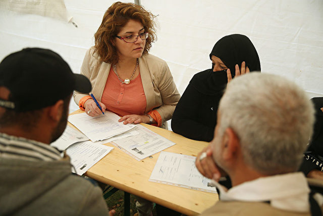 BERLIN, GERMANY - SEPTEMBER 08:  A translator helps a family from Syria fill out application forms for refugee status in a makeshift office in a tent outside the Berlin Central Reception Facility for Asylum Seekers (in German: Zentrale Aufnahmeeinrichtung des Landes Berlin fuer Asylbewerber (ZAA)) on September 8, 2014 in Berlin, Germany. The Berlin facility, even though it recently hired additional personnel, has been so overwhelmed new applicants that it closed its doors on September 3 in order to process backlogged applications and only reopened today. Many German cities are facing a surge in the numbers of refugees arriving from abroad, especially from Africa, Syria and the Balkans.  (Photo by Sean Gallup/Getty Images)