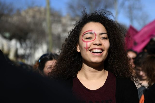 A woman with the female gender pictogram made up on her face attends a demonstration as part of the 40th International Women's Day on March 8, 2017 in Marseille.  / AFP PHOTO / ANNE-CHRISTINE POUJOULAT        (Photo credit should read ANNE-CHRISTINE POUJOULAT/AFP/Getty Images)