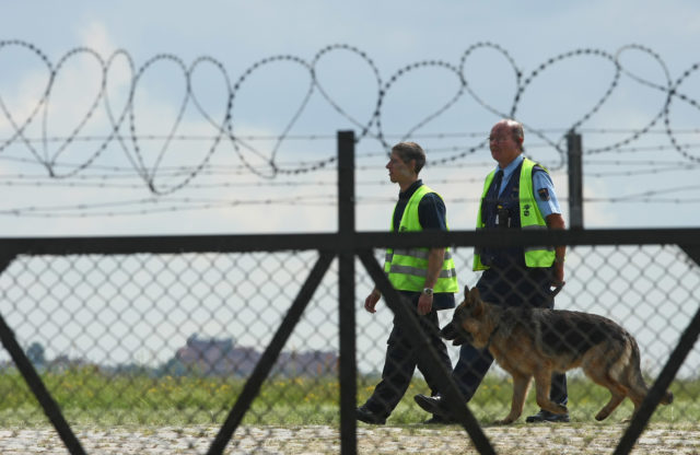 "BERLIN - JUNE 20:  Security guards with a dog patrol the perimeter fence of former Tempelhof airport on June 20, 2009 in Berlin, Germany. Police are expecting up to 10,000 left-wing protesters to attempt to storm the grounds of the former airport, and claim to have 1,800 police officers on hand to prevent them. The protesters, led by the organization ""Squat Tempelhof,"" demand the immediate opening of the aiport grounds to public access.    (Photo by Sean Gallup/Getty Images)"