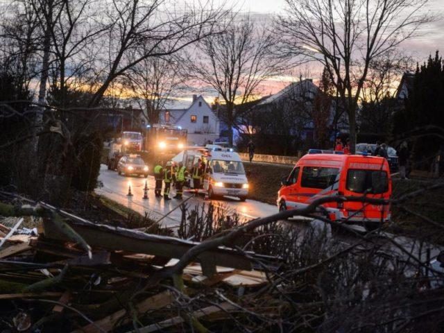 Feuerwehrleute und Anwohner räumen in einem Wohngebiet die Schäden auf. Foto: Daniel Peter/dpa