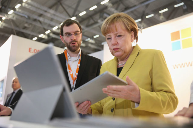 COLOGNE, GERMANY - DECEMBER 10:  German Chancellor and Chairwoman of the German Christian Democrats (CDU) Angela Merkel looks at a tablet computer at the Microsoft stand while visiting exhibitors at the annual CDU party congress on December 10, 2014 in Cologne, Germany. The CDU is the senior partner in Germany's ruling government coalition and yesterday delegates re-elected Merkel as party chairwoman with 96.7% of votes.  (Photo by Sean Gallup/Getty Images)