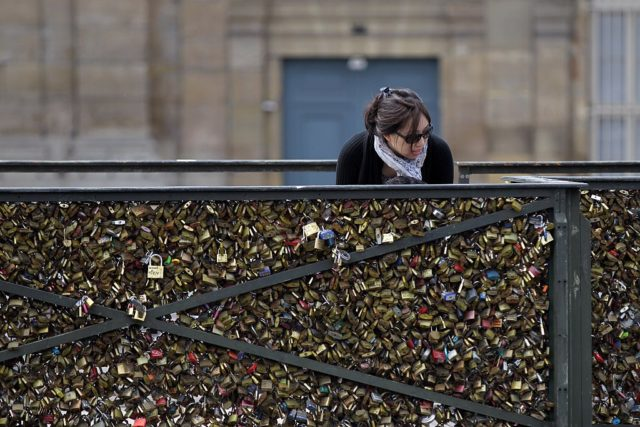 "A woman looks at padlocks hanging on the ""Pont des Arts"" on May 29, 2015 in Paris as the Paris municipalty announced that the bridge fences have to be removed due to the weight of the padlocks put by tourists to ensure everlasting love. AFP PHOTO / CHARLY TRIBALLEAU (Photo credit should read CHARLY TRIBALLEAU/AFP/Getty Images)"