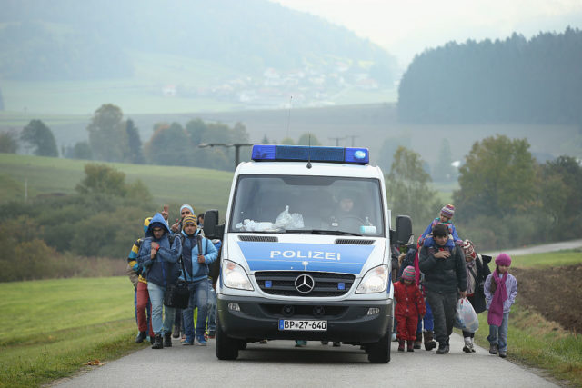WEGSCHEID, GERMANY - OCTOBER 17:  A German police van escorts migrants who had just crossed into Germany from Austria on October 17, 2015 near Wegscheid, Germany. According to a German police spokesman approximately 6,000 migrants are arriving daily over the border just in the area of southeastern Bavaria near the city of Passau. Most arrive via the Balkan route and once in Austria are transported by Austrian authorities to locations near the border to Germany. Germany has reportedly registered over 800,000 migrants this year, 400,000 in September alone. The migrants include many refugees from countries including Syria, Afghanistan and Iraq. Germany is struggling to accommodate the many migrants, most of whom will apply for asylum.  (Photo by Sean Gallup/Getty Images)
