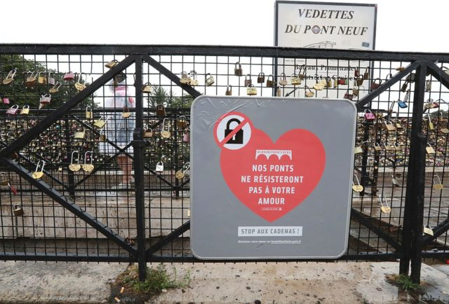 "A placard reading ""our bridges won't resist your love"", is seen among ""love-locks"" hung on the bridge of Pont Neuf in Paris, on August 4, 2016. Love may know no bounds, but Paris intends to instill some: authorities are going to take a tougher line with swooning couples attaching ""love-locks"" to city bridges as a sign of their undying devotion. In June last year authorities removed hundreds of thousands of such padlocks from the city bridges, notably the Pont des Arts which had a section collapse under the weight of the locks. / AFP / JACQUES DEMARTHON (Photo credit should read JACQUES DEMARTHON/AFP/Getty Images)"