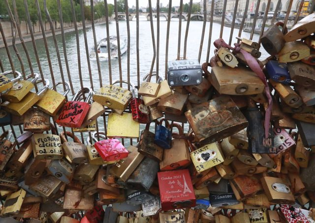 "Love-locks are seen on the footbridge of Leopold-Sedar-Senghor in Paris, on August 4, 2016. Love may know no bounds, but Paris intends to instill some: authorities are going to take a tougher line with swooning couples attaching ""love-locks"" to city bridges as a sign of their undying devotion. In June last year authorities removed hundreds of thousands of such padlocks from the city bridges, notably the Pont des Arts which had a section collapse under the weight of the locks. / AFP / JACQUES DEMARTHON (Photo credit should read JACQUES DEMARTHON/AFP/Getty Images)"