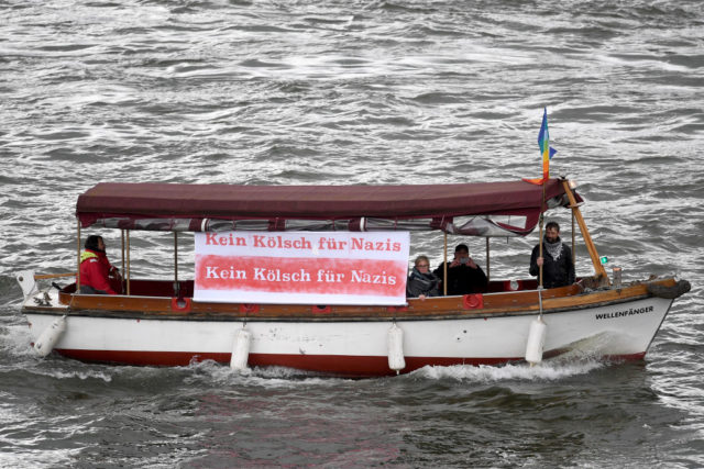 COLOGNE, GERMANY - APRIL 22: A boat with a sign reading 'No Koelsch for Nazis' passes by a demonstration against the right-wing populist Alternative for Germany (AfD) political party march in the city center not far from where the AfD was holding its federal congress on April 22, 2017 in Cologne, Germany. Up to 50,000 people were expected to participate in the protests against the AfD, which is holding its federal congress of delegates following the recent surprise announcement by its chairwoman Frauke Petry that she will not run in German federal elections scheduled for September. The AfD saw a surge in popularity that helped it capture seats in 10 state parliaments, though more recently that party has seen its poll numbers slip. It has also been plagued by infighting between more moderate and radical factions of its leadership. (Photo by Lukas Schulze/Getty Images)