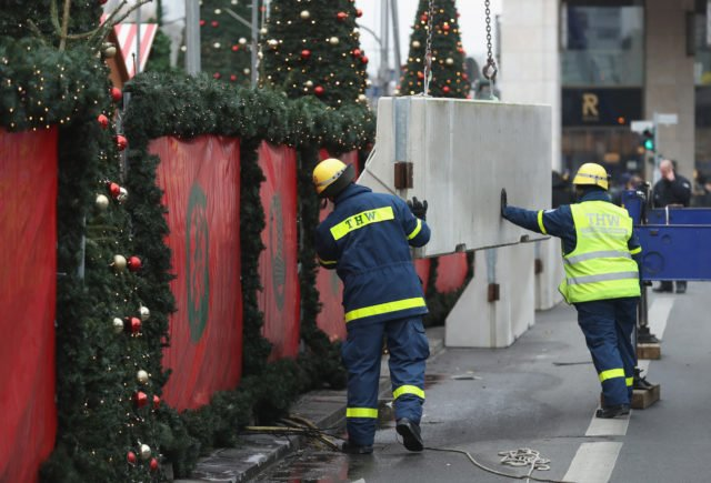 BERLIN, GERMANY - DECEMBER 22:  Workers install concrete blocks as a security barrier on the periphery of the reopened Breitscheidplatz Christmas market, where three days ago a truck plowed into the market, killed 12 people and injured dozens in a terrorist attack on December 22, 2016 in Berlin, Germany. The Breidscheidplatz Christmas market is reopening today, though its small amusement rides and bright lights displays will remain shut off in a sign of continuing mourning for the attack victims. Meanwhile police have launched a European-wide manhunt for Anis Amri, a 24-year-old Tunisian man they suspect of having driven the truck.  (Photo by Sean Gallup/Getty Images)