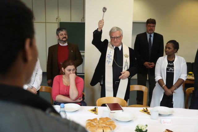 SCHOENEICHE, GERMANY - FEBRUARY 24: Berlin Archbishop Heiner Koch blesses the dining room of a refugees and migrants shelter as residents look on during a visit on February 24, 2017 in Schoeneiche, Germany. Koch blessed rooms in the facility, which is run by the Catholic charity Caritas, and spoke with some of the 83 residents, who are from countries including Syria, Eritrea, Afghanistan, Cameroon, Chechnya and Pakistan. Germany took in over one million refugees and migrants in 2015-2016. (Photo by Sean Gallup/Getty Images)