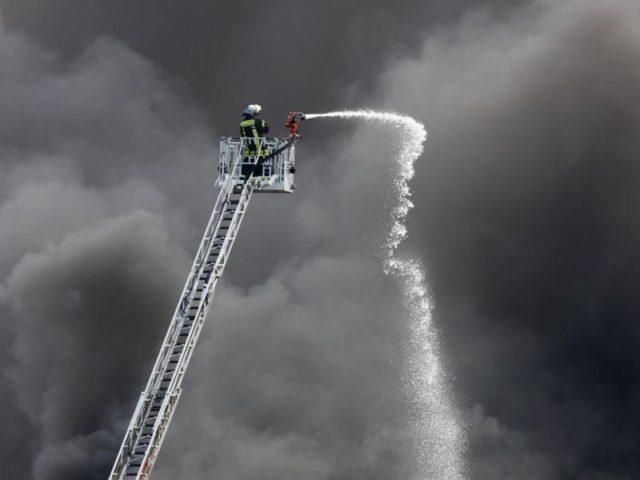 Ein Feuerwehrmann löscht einen Brand bei einer Kunststofffirma in Magdeburg. Das Feuer brach wohl in einer Halle aus. Foto: Peter Gercke/dpa