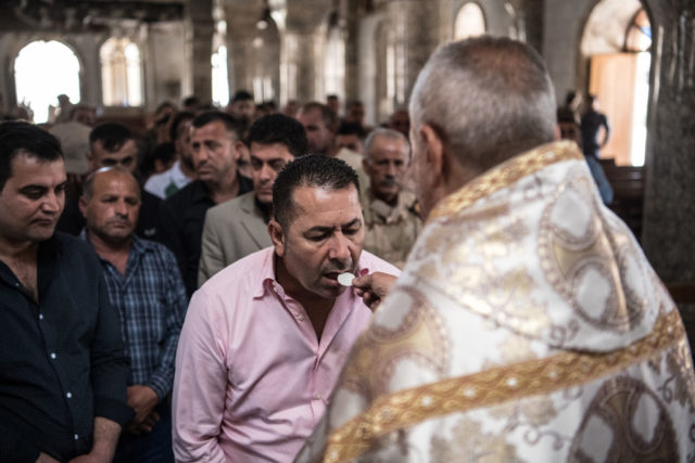 MOSUL, IRAQ - APRIL 16: Iraqi Syriac Christian priest Charbel Aesso gives the Eucharist during an easter service at Saint John's Church (Mar Yohanna) in the nearly deserted predominantly Christian Iraqi town of Qaraqosh on April 16, 2017 near Mosul, Iraq. Qaraqosh was retaken by Iraqi forces in 2016 during the offensive to capture the nearby city of Mosul from Islamic State but it remains almost completely deserted. (Photo by Carl Court/Getty Images)