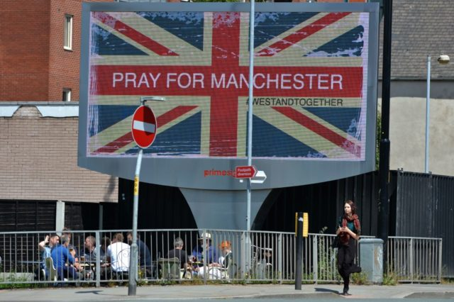 "TOPSHOT - A woman walks past an electronic advertising board displaying a Union flag and the words ""Pray For Manchester"", close to the Manchester Arena in Manchester, northwest England on May 23, 2017, following a deadly terror attack at an Ariana Grande concert at the Manchester Arena on May 22. Twenty two people have been killed and dozens injured in Britain's deadliest terror attack in over a decade after a suspected suicide bomber targeted fans leaving a concert of US singer Ariana Grande in Manchester. / AFP PHOTO / Ben Stansall        (Photo credit should read BEN STANSALL/AFP/Getty Images)"