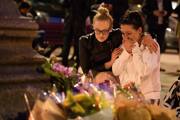 MANCHESTER, ENGLAND - MAY 23:  A woman is consoled as she looks at the floral tributes following an evening vigil outside the Town Hall on May 23, 2017 in Manchester, England. An explosion occurred at Manchester Arena as concert goers were leaving the venue after Ariana Grande had performed. Greater Manchester Police are treating the explosion as a terrorist attack and have confirmed 22 fatalities and 59 injured.  (Photo by Leon Neal/Getty Images)