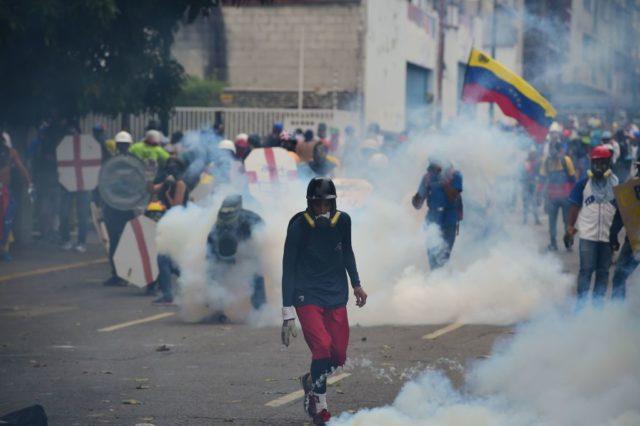 Demonstranten in Wolken von Tränengas, das von der Polizei abgeschoßen wurde. Foto: RONALDO SCHEMIDT/AFP/Getty Images