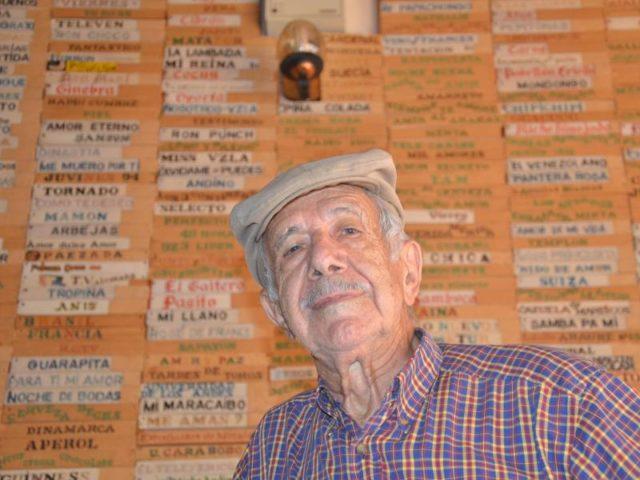 Eisdielenbesitzer Manuel da Silva Oliveira in Mérida (Venezuela) unter der Tafel mit den Eissorten. Foto: Georg Ismar/dpa