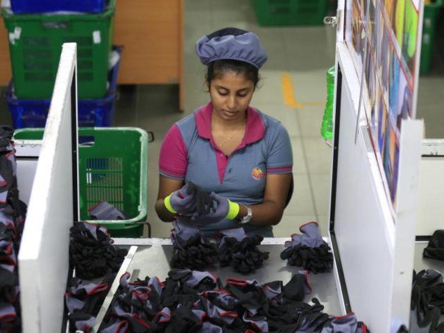 Eine Frau arbeitet in der Nähe von Colombo (Sri Lanka) in einer Handschuhfabrik. Foto: Eranga Jayawardena/dpa