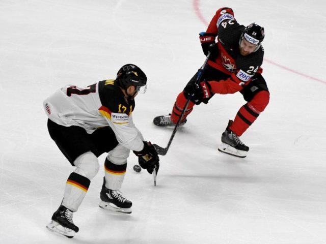 Kanadas Calvin de Haan (r) und Deutschlands Marcus Kink kämpfen um den Puck. Foto: Monika Skolimowska/dpa
