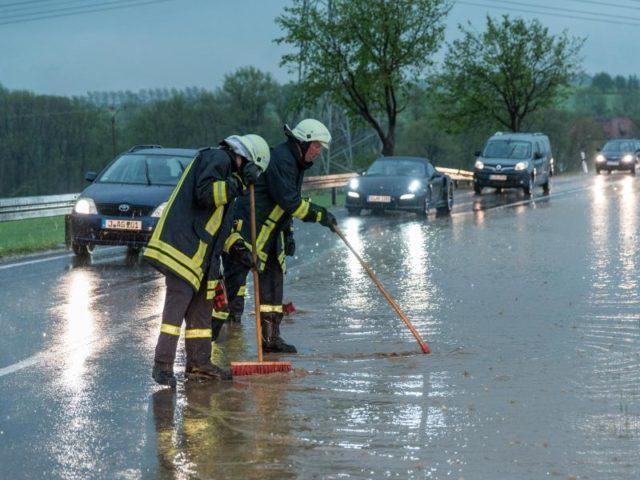 Feuerwehrleute versuchen die Wassermassen von der überschwemmten Bundesstraße B7 zwischen Weimar und Jena zu beseitigen. Foto: Johannes Krey/dpa