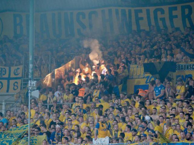 Braunschweiger Fans brennen auf der Tribüne Feuerwerkskörper ab. Foto: Peter Steffen/dpa