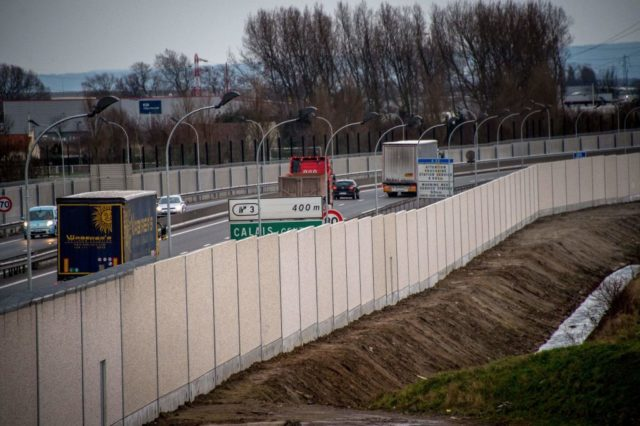 A photo taken on February 2, 2017 in Calais, shows trucks on a road next to a four-metre-high (13-foot) wall, running along a kilometre-long stretch of the main road leading to Calais port, aimed at stopping migrants who attempt to reach its shores. The wall was built to boost a network of wire fences that had failed to prevent near nightly attempts by migrants to waylay trucks en route to Europe's second-busiest port. Calais has for years been a staging post for attempts by migrants to sneak into Britain by stowing away on trucks or trains crossing the Channel. / AFP / PHILIPPE HUGUEN (Photo credit should read PHILIPPE HUGUEN/AFP/Getty Images)
