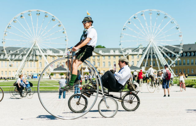 KARLSRUHE, GERMANY - MAY 27: Participants dressed in historical clothing ride high-wheel bicycles during a bicycle ballet event at Schloss Karlsruhe palace during the 2017 International Veteran Cycle Association (IVCA) rally to celebrate the 200th anniversary of the bicycle on May 27, 2017 in Karlsruhe, Germany. Karl Drais, a German inventor, built and tested the first bicycle, called the Draisine, that ran without pedals in 1817. (Photo by Alexander Scheuber/Getty Images)