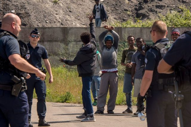 Migrants raise their arms in front of a French police officer on June 1, 2017, in Calais. Migrants set brushwoods on fire on the A16 highway late on May 31, 2017, near Calais, northern France. / AFP PHOTO / PHILIPPE HUGUEN (Photo credit should read PHILIPPE HUGUEN/AFP/Getty Images)