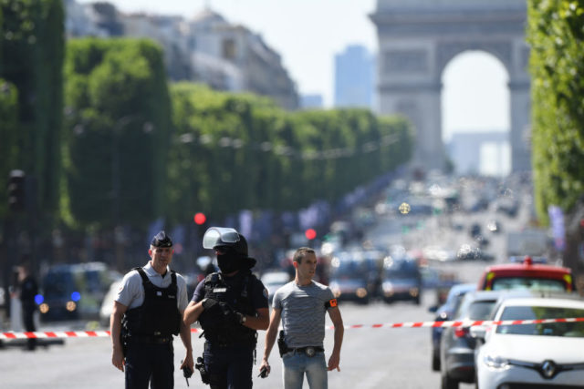 Policemen stand guard, on June 19, 2017 on the Champs-Elysees avenue in Paris, after a car crashed into a police van before bursting into flames, with the driver being armed, probe sources said.  / AFP PHOTO / ALAIN JOCARD        (Photo credit should read ALAIN JOCARD/AFP/Getty Images)