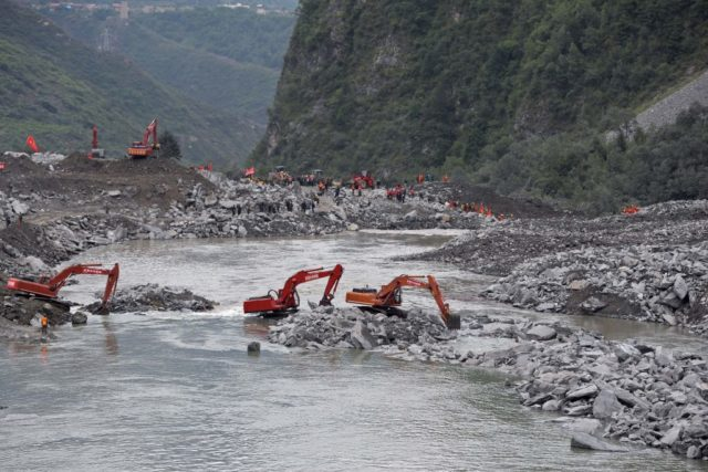 In this photo taken on June 25, 2017, rescue workers are seen at the site of a landslide in Xinmo village, Diexi town of Maoxian county, Sichuan province.  Rescuers searching for more than 90 people missing following the huge landslide in southwest China were ordered to evacuate on June 26 due to the risk of another collapse, state media reported. / AFP PHOTO / STR / China OUT        (Photo credit should read STR/AFP/Getty Images)