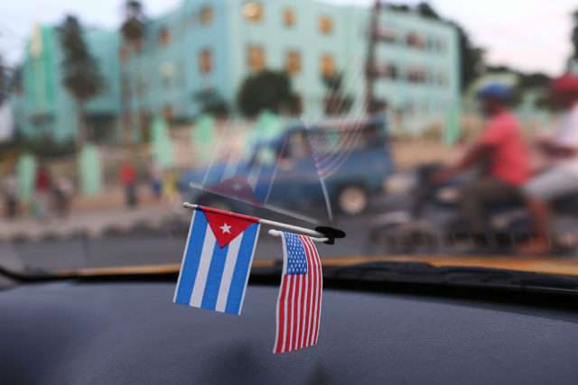 SANTIAGO DE CUBA, CUBA - SEPTEMBER 18: A Cuban and American flag are seen in the window of a taxi as Cuba prepares to welcome Pope Francis for a visit on September 18, 2015 in Santiago de Cuba, Cuba. Pope Francis is due to make a three day visit to Cuba from September 19 where he will meet President Raul Castro and hold Mass in Revolution Square before travelling to Holguin, Santiago de Cuba, El Cobre and onwards to the United States. (Photo by Joe Raedle/Getty Images)