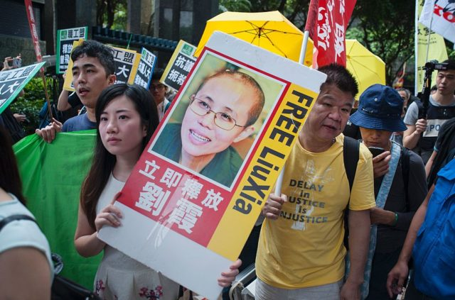 A protester (centre L) holds a placard calling for the release of Chinese human rights activist Liu Xiaobo (pictured C) as she joins a march in the Wanchai district of Hong Kong on May 18, 2016 calling for universal suffrage and an end to arrests of activists in China as a top Beijing official visits the city. The protest coincided with three-day trip by Zhang Dejiang, who chairs China's communist-controlled legislature, and is the first by such a senior official in four years and comes as concerns grow that freedoms are under threat in semi-autonomous city. / AFP / Richard A. Brooks (Photo credit should read RICHARD A. BROOKS/AFP/Getty Images)
