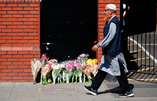 A man walks past floral tributes outside Finsbury Park Mosque in the Finsbury Park area of north London, on June 19, 2017, near to where a vehicle was driven into pedestrians.  Ten people were injured when a van drove into a crowd of Muslim worshippers near a mosque in London in the early hours of Monday, and a man who had been taken ill before the attack died at the scene. / AFP PHOTO / Tolga AKMEN        (Photo credit should read TOLGA AKMEN/AFP/Getty Images)