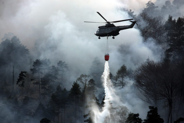 """BAD REICHENHALL, GERMANY - APRIL 13:  A police helicopter releases water to fight a mountain forest fire on April 13, 2007, Bad Reichenhall, Germany. Peggy"""", a high pressure system with unusually warm, summerlike temperatures and dry air is responsible for a chain of forest fires in southern Bayern and in the Austrian Alps. The fire near Bad Reichenhall is spread over an area of 50.000 hectars. (Photo by Johannes Simon/Getty Images)"""