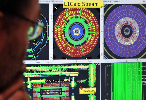 "A European Organization for Nuclear Research (CERN) scientist looks at computer screens showing traces on the Atlas experiment of the first protons injected in the Large Hadron Collider (LHC) during its switch-on operation at the Cern's press center on September 10, 2008 near Geneva. Particle physicists fired up the world's biggest atom-smasher in a mission to answer some of the most perplexing questions about the nature of the Universe. Built in a tunnel 100 metres (325 feet) below ground in a complex straddling the French-Swiss border, the LHC is designed to accelerate sub-atomic particles to nearly the speed of light and then smash them together replicating conditions which prevailed in split-seconds after the ""Big Bang"" that created the Universe 13.7 billion years ago. AFP PHOTO / FABRICE COFFRINI/POOL (Photo credit should read FABRICE COFFRINI/AFP/Getty Images)"