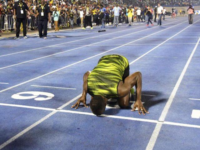 Usain Bolt küsst nach seinem Sieg beim «Racers Grand Prix» zum Abschied die Ziellinie der Tartanbahn in Kingston. Foto: Bryan Cummings/dpa