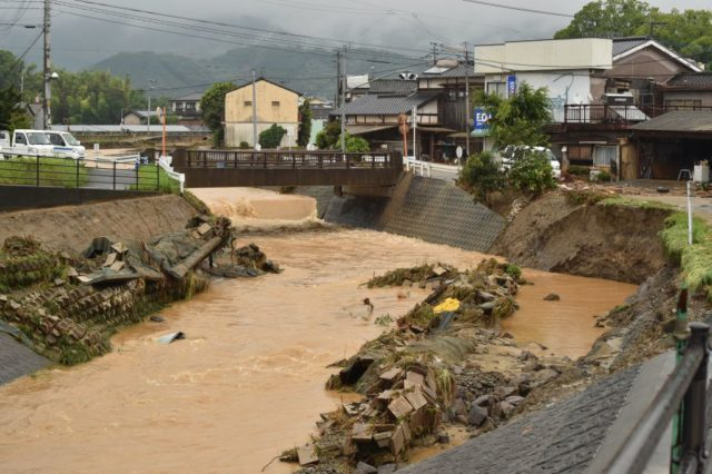 An inundated river flows following heavy flooding in Asakura, Fukuoka prefecture, on July 6, 2017. At least two people have been killed and 18 others are missing in huge floods that are surging through southern Japan, with authorities warning hundreds of thousands of people to flee. / AFP PHOTO / KAZUHIRO NOGI (Photo credit should read KAZUHIRO NOGI/AFP/Getty Images)