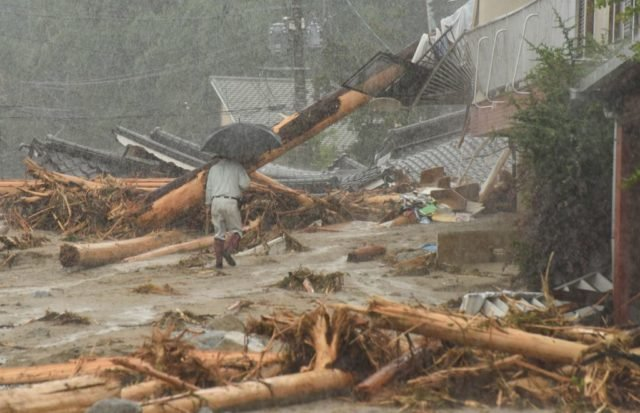 TOPSHOT - A resident walks past collapsed houses following heavy flooding in Asakura, Fukuoka prefecture, on July 7, 2017. Huge floods engulfing parts of southern Japan are reported to have killed at least six people and left hundreds stranded as the torrents swept away roads and houses and destroyed schools. / AFP PHOTO / KAZUHIRO NOGI (Photo credit should read KAZUHIRO NOGI/AFP/Getty Images)
