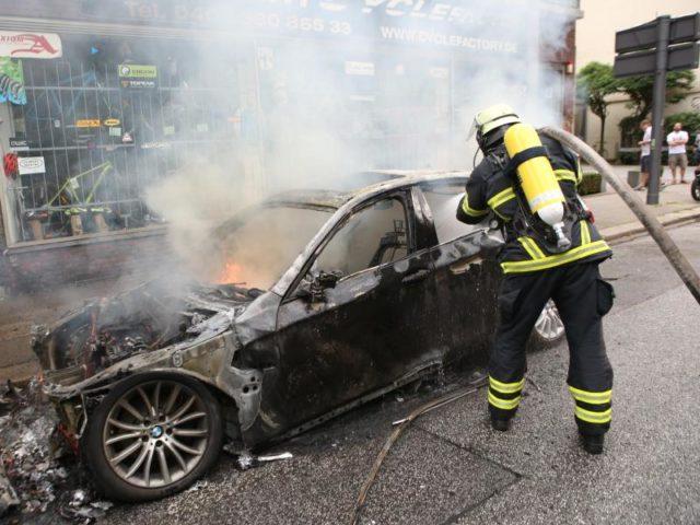 Ein Feuerwehrmann löscht in Altona ein brennendes Auto. Foto: Bodo Marks/dpa