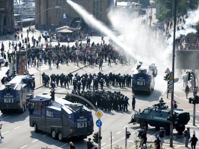 Bilder wie in einem Bürgerkrieg: Vor den Hamburger Landungsbrücken treffen Polizisten und Demonstranten aufeinander. Foto: Daniel Reinhardt/dpa