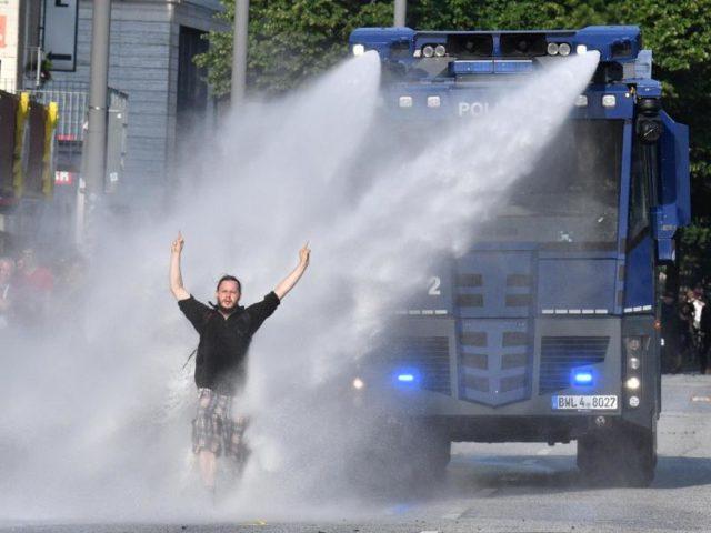 Ein Demonstrant stellt sich im Bereich der Reeperbahn in Hamburg einem Wasserwerfer entgegen. Foto: Boris Roessler/dpa