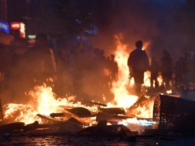 Aktivisten stehen im Hamburger Schanzenviertel vor einer brennenden Barrikade. Foto: Boris Roessler/dpa