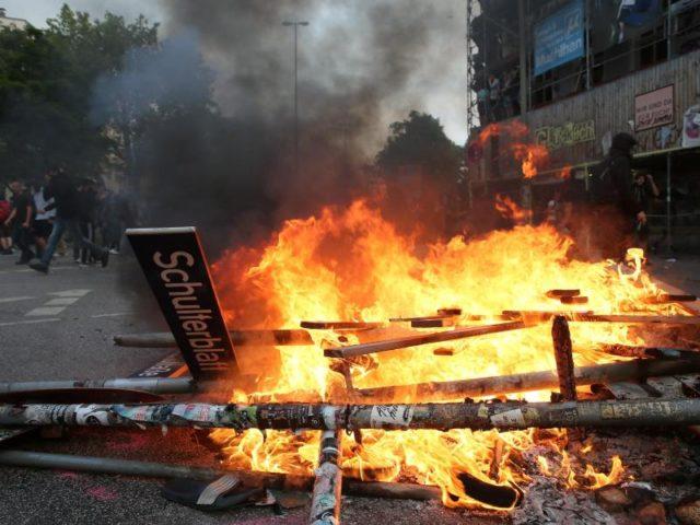 Verwüstung,Zerstörung,Gewalt. Ein herausgerissenes Straßenschild liegt in den Flammen. Foto: Markus Scholz/dpa