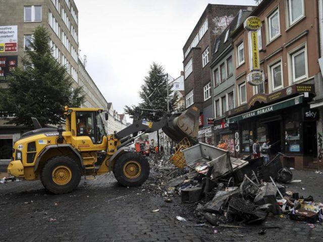 Mitarbeiter der Stadtreinigung säubern in Hamburg die Straße Schulterblatt im Schanzenviertel von den Verwüstungen aus der Nacht. Foto: Christian Charisius/dpa