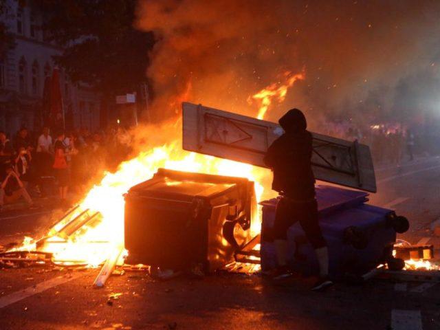 Ein Randalierer wirft einen Biertisch in eine brennende Barrikade. Foto: Bodo Marks/Archiv/dpa