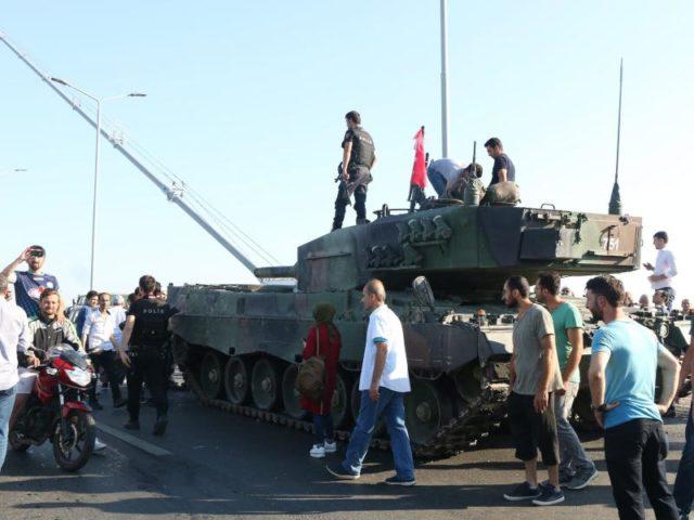 Türkische Polizisten und Anhänger von Präsident Erdogan stehen nach dem gescheiterten Putsch in der Nähe von Panzern auf der Bosporusbrücke in Istanbul. Foto: str/dpa