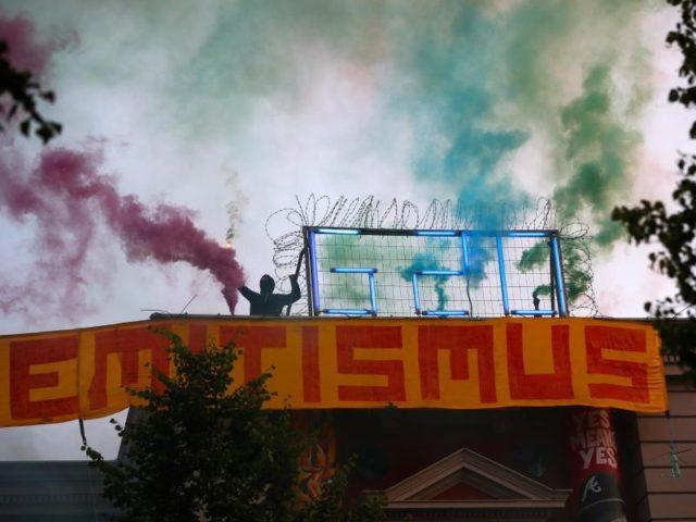 Während des G20-Gipfels:Autonomer mit Bengalos auf dem Dach der Roten Flora. Foto:Christian Charisius/dpa